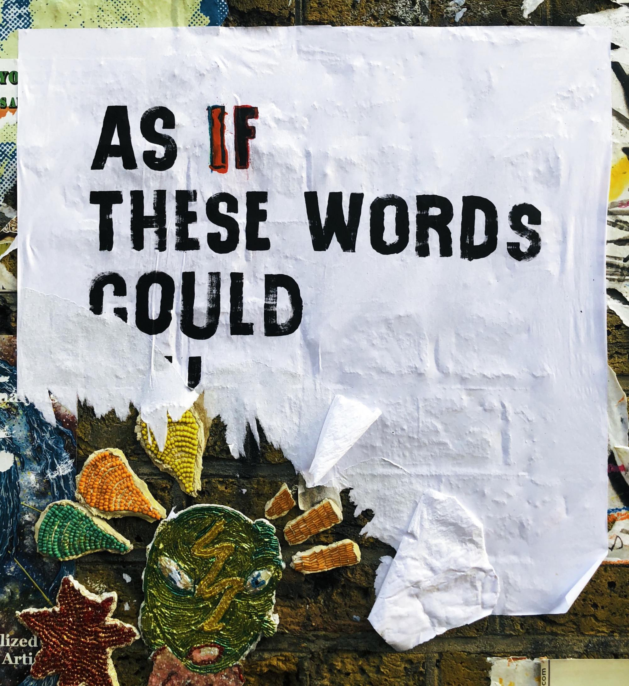 Ripped billboard where only the words: 'As If These Words Could' can be seen